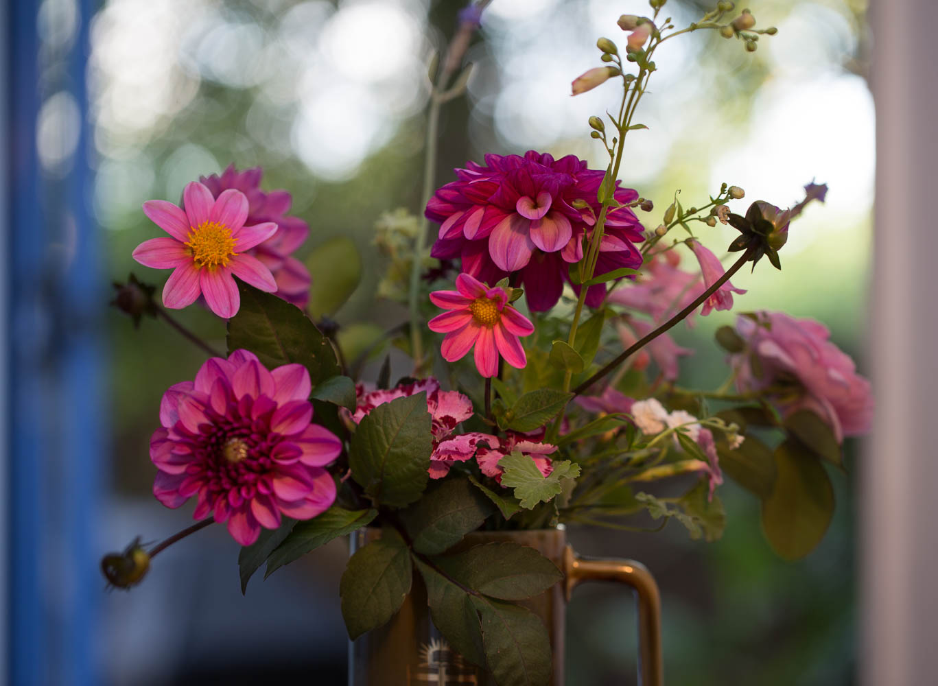 pink dahlias and roses in a vase