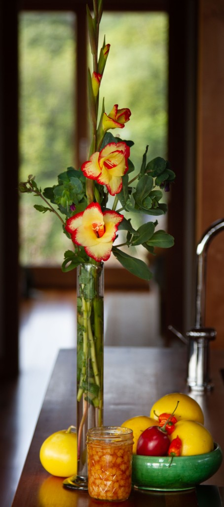 Miniature gladiolus in a vase with winter fruits
